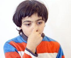 あまりの臭い匂いに鼻をつまむ少年