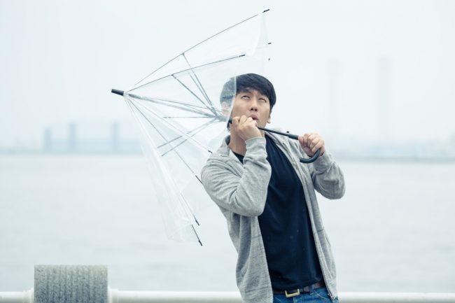 なぐり雨の中、傘をさす男性
