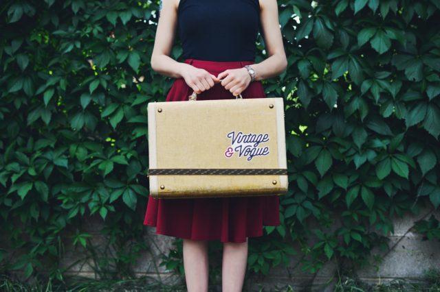 キャリーバッグを両手で持つ女性