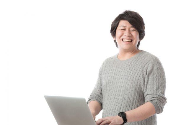 パソコン作業をしながら陽気な男