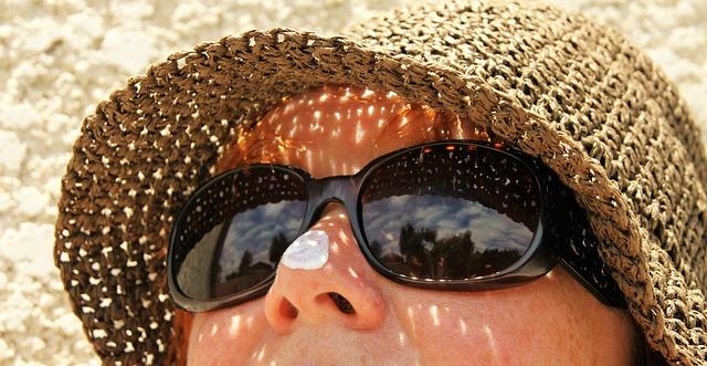 日焼け止めを塗って、日光浴をする女性